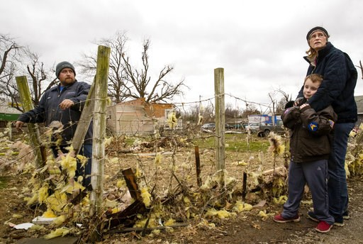 (Ted Schurter/The State Journal-Register via AP). David Bowers, left, his son David and wife Tammy gather at the edge of their property in Taylorville, Ill., after assessing the tornado damage to their home Sunday, Dec. 2, 2018. The family took shelter...