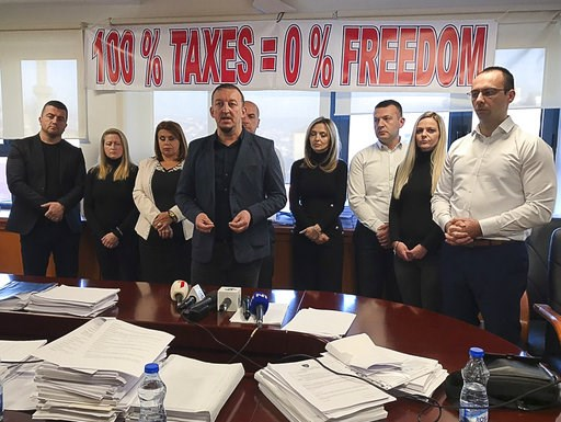 (AP Photo/Florent Bajrami). Kosovo Serb MP's stand in protest as they refuse to leave the Kosovo parliament building to protest against the 100 percent tax imposed on all goods imported from Serbia, in Pristina, Sunday Dec. 2, 2018.  The group said the...