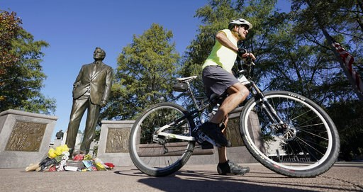 (AP Photo/David J. Phillip). A bicyclist passes by a statue of former President George H.W. Bush in downtown Houston, Sunday, Dec. 2, 2018. Bush is returning to Washington as a revered political statesman, hailed by leaders across the political spectru...