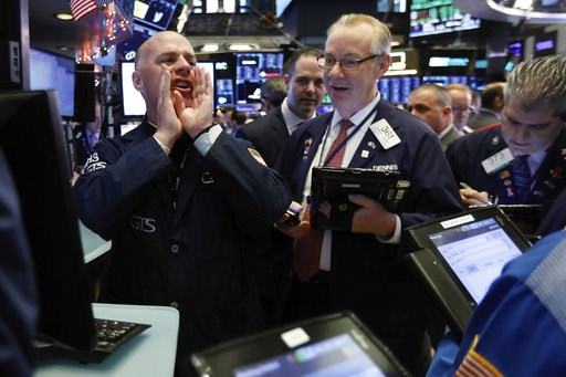 (AP Photo/Richard Drew). In this Thursday, Nov. 29, 2018, photo, specialist John O'Hara, left, works with traders at his post on the floor of the New York Stock Exchange. The new cease-fire in the trade dispute between the U.S. and China should boost r...