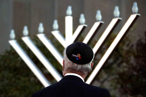 (AP Photo/Gene J. Puskar). Rabbi Jeffrey Myers watches the installation of a menorah outside the Tree of Life Synagogue before holding a celebration on the first night of Hanukkah, Sunday, Dec. 2, 2018, in the Squirrel Hill neighborhood of Pittsburgh. ...