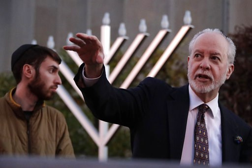 (AP Photo/Gene J. Puskar). Rabbi Jeffrey Myers, right and his son Aaron oversee the installation of a menorah outside the Tree of Life Synagogue before holding a celebration on the first night of Hanukkah, Sunday, Dec. 2, 2018 in the Squirrel Hill neig...