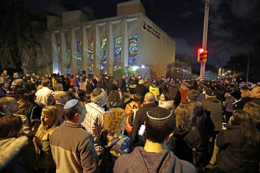 (AP Photo/Gene J. Puskar). Rabbi Jeffrey Myers leads a gathering in Hanukkah songs after lighting a menorah outside the Tree of Life Synagogue on the first night of Hanukkah, Sunday, Dec. 2, 2018 in the Squirrel Hill neighborhood of Pittsburgh. A gunma...