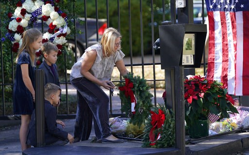 (AP Photo/David J. Phillip). Tiffany Utterson, right, and her children, from left to right, Ella, 11, Ian, 10 and Owen, 8, place a wreath outside the gated community entrance to the home of George H.W. Bush Sunday, Dec. 2, 2018, in Houston. Bush is ret...