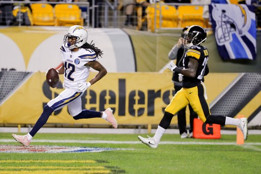 (AP Photo/Gene J. Puskar). Los Angeles Chargers wide receiver Travis Benjamin (12) dashes past Pittsburgh Steelers cornerback Mike Hilton (28) on his way to a touchdown after making a catch in the first half of an NFL football game, Sunday, Dec. 2, 201...