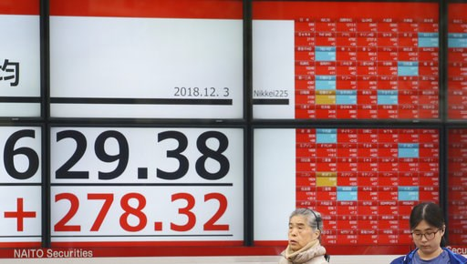 (AP Photo/Koji Sasahara). People stand by an electronic stock board of a securities firm in Tokyo, Monday, Dec. 3, 2018. Shares are advancing in Asia following the meeting between Presidents Donald Trump and Xi Jinping, who agreed moderate tensions ove...