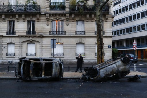 (AP Photo/Thibault Camus). A man takes a snapshot of charred cars the day after a demonstration, near the Arc de Triomphe, in Paris, Sunday, Dec. 2, 2018. A protest against rising taxes and the high cost of living turned into a riot in the French capit...