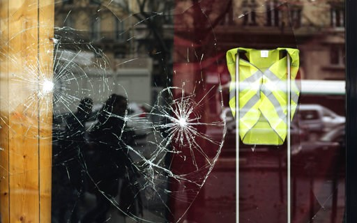 (AP Photo/Kamil Zihnioglu). A smashed window displays a yellow vest, showing support for protesters and for protesters not to attack the building, near the Arc de Triomphe, in Paris, Sunday, Dec. 2, 2018. A protest against rising taxes and the high cos...