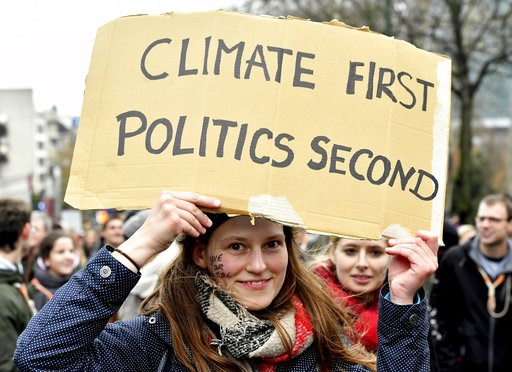 (AP Photo/Geert Vanden Wijngaert). A demonstrator holds a placard which reads 'climate first, politics second' during a 'Claim the Climate' march in Brussels, Sunday, Dec. 2, 2018. The climate change conference, COP24, will take place in Poland from De...