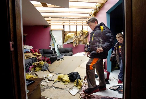 (Ted Schurter/The State Journal-Register via AP). Tim Mayes and his cousin David Bowers step gingerly through the interior of Bowers' tornado-damaged Taylorville, Ill. home Sunday, Dec. 2, 2018. The roof of their home was completely torn off by the sto...