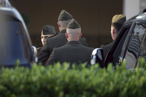 (AP Photo/Kiichiro Sato). Members of a color guard gather outside the George H. Lewis Funeral Home as they prepare for a departure ceremony for the state funeral for former President George H.W. Bush, Monday, Dec. 3, 2018, in Houston.