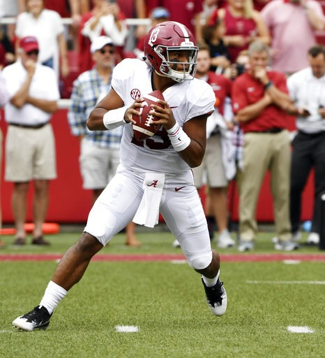 (AP Photo/Michael Woods, File). FILE - In this Oct. 6, 2018, file photo, Alabama quarterback Tua Tagovailoa rolls out before throwing a touchdown pass on the first play of the game against Arkansas in the first half of an NCAA college football game, in...