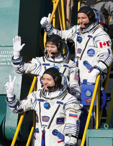 (AP Photo/Shamil Zhumatov, Pool). U.S. astronaut Anne McClain, centre, Russian cosmonaut ?leg Kononenko, bottom, and CSA astronaut David Saint Jacques, crew members of the mission to the International Space Station, ISS, wave as they board the rocket p...