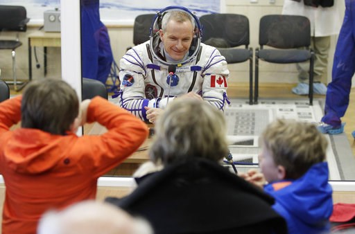 (AP Photo/Dmitri Lovetsky, Pool). CSA astronaut David Saint Jacques, member of the main crew of the expedition to the International Space Station (ISS), speaks with his relatives through a safety glass prior to the launch of Soyuz MS-11 space ship at t...