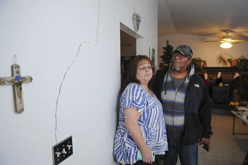 (AP Photo/Michael Dinneen). Al and Lyn Matthews show structural cracks in their home in south Anchorage, Alaska, following earthquakes Friday, Nov. 30, 2018.