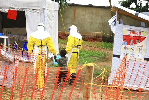 (AP Photo/Al-hadji Kudra Maliro, FILE). FILE - In this file photo dated Sunday, Sept. 9, 2018, health workers walk with a boy suspected as having the Ebola virus at an Ebola treatment centre in Beni, Eastern Congo.  According to a WHO announcement Thur...