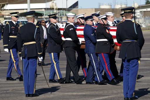 (AP Photo/David J. Phillip, Pool). The flag-draped casket of former President George H.W. Bush is carried by a joint services military honor guard to Special Air Mission 41 at Ellington Field during a departure ceremony Monday, Dec. 3, 2018, in Houston.