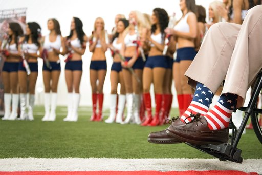 (Smiley N. Pool/Houston Chronicle via AP, File). Former President George H.W. Bush wears American flag socks as he presents roses to the new Houston Texans cheerleaders during a ceremony introducing the new squad at the team's NFL football training fac...