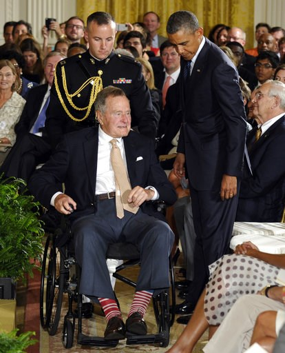 (AP Photo/Susan Walsh, File). Former President George H.W. Bush, in a pair of red and white socks, is wheeled off of the stage to sit next to President Barack Obama after presenting the 5,000th Daily Point of Light Award at the White House in Washingto...