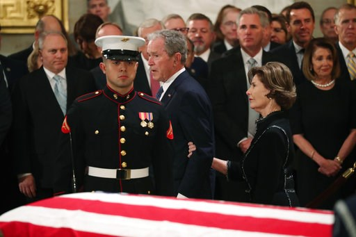 (Jonathan Ernst/Pool Photo via AP). Former President George W. Bush, with his wife former first lady Laura, walks past the casket of his father, former President George H.W. Bush at the Capitol in Washington, Monday, Dec. 3, 2018.