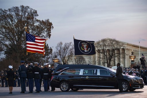 (Shawn Thew/Pool Photo via AP). A joint services military honor guard removes the casket of former President George H.W. Bush from the hearse to carry it into the rotunda of the U.S. Capitol in Washington to lie in state, Monday, Dec. 3, 2018.