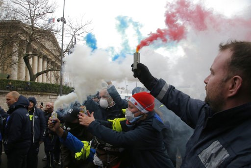 (AP Photo/Michel Euler). Ambulance workers hold flares outside the National Assembly in Paris, Monday, Dec. 3, 2018. Ambulance workers took to the streets and gathered close to the National Assembly in downtown Paris to complain about changes to workin...