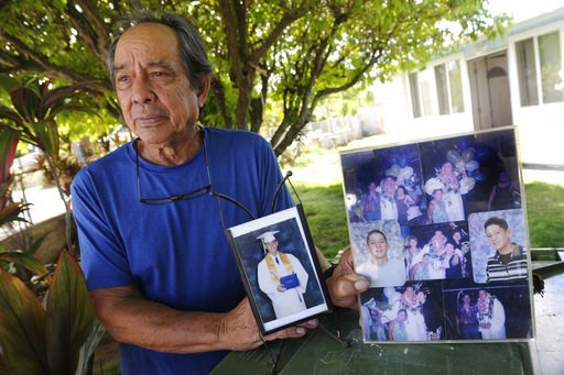 (Bruce Asato/Honolulu Star-Advertiser via AP, File). FILE - In this July 10, 2017, file photo, Clifford Kang, father of soldier Ikaika E. Kang, poses with photos of his son in Kailua, Hawaii. Ikaika E. Kang, an active-duty U.S. soldier, arrested on ter...