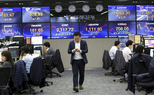 (AP Photo/Ahn Young-joon). A currency trader watches his mobile phone at the foreign exchange dealing room of the KEB Hana Bank headquarters in Seoul, South Korea, Tuesday, Dec. 4, 2018. Asian shares were mostly lower Tuesday as investors wondered if a...