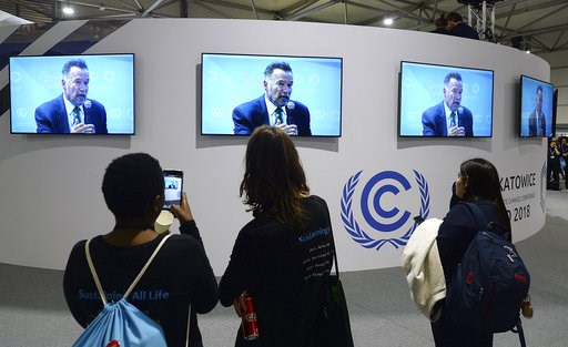 (AP Photo/Czarek Sokolowski). Visitors to the U.N. climate conference watch a speech by Arnold Schwarzenegger, in Katowice, Poland, Monday, Dec. 3, 2018. The COP24 UN Climate Change Conference is taking place in Katowice, Poland. Negotiators from aroun...