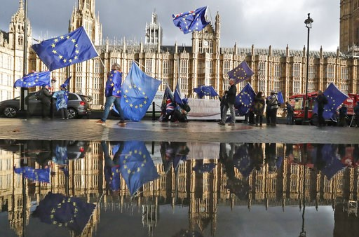 (AP Photo/Frank Augstein). Protestors are reflected in a puddle as they wave European flags to demonstrate against Brexit in front of the Parliament in London, Monday, Dec. 3, 2018.