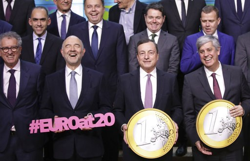 (AP Photo/Olivier Matthys). European Central Bank President Mario Draghi, front second right, and Portuguese Economy Minister Mario Centeno, center right, hold giant euro coins during a group photo of EU finance ministers in Brussels, Monday, Dec. 3, 2...