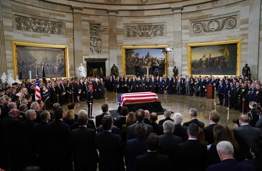 (AP Photo/Pablo Martinez Monsivais/Pool). The flag-draped casket of former President George H.W. Bush lies in state in the Capitol Rotunda in Washington, Monday, Dec. 3, 2018.