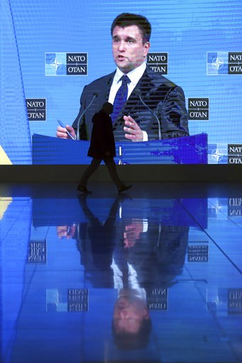 (AP Photo/Francisco Seco). A man walks by a large screen projecting the media conference of Ukraine's Foreign Minister Pavlo Klimkin after a meeting of NATO foreign ministers at NATO headquarters in Brussels, Tuesday, Dec. 4, 2018. Russia takes center-...