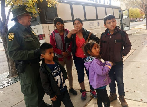 (AP Photo/Russell Contreras). In this Thursday, Nov. 29, 2018 photo, a migrant family from Central America waits outside the Annunciation House shelter in El Paso, Texas, after a U.S. Immigration and Customs Enforcement officer drops them off. Voluntee...