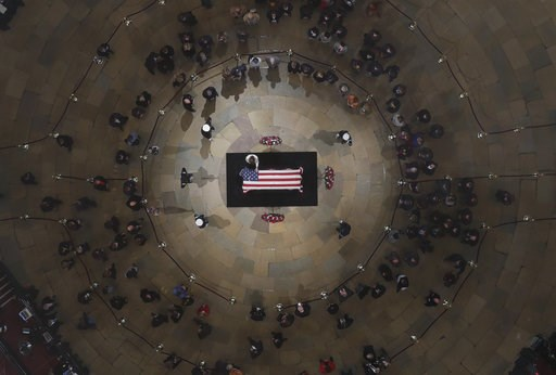 (Pool photo by Morry Gash via AP). A mourner puts a hand on the flag-draped casket of former President George H. W. Bush as he lies in state in the U.S. Capitol Rotunda Tuesday, Dec. 4, 2018, in Washington.