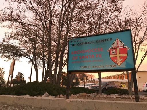 (AP Photo/Susan Montoya Bryan). The sun sets on a sign in front of the Archdiocese of Santa Fe offices in Albuquerque, N.M., on Thursday, Nov. 29, 2018. Archbishop John Wester announced Thursday that the archdiocese will be filing for Chapter 11 bankru...