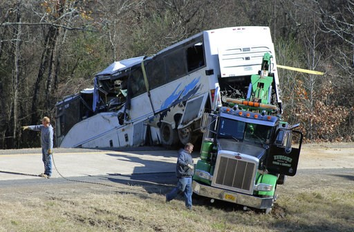 (Josh Briggs/Saline Courier via AP). Employees from a wrecker service work to remove a charter bus from a roadside ditch Monday, Dec. 3, 2018, after it crashed alongside Interstate 30 near Benton, Ark. The bus was carrying a youth football team from Te...