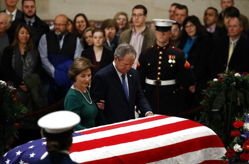 (AP Photo/Patrick Semansky). Former President George W. Bush and former first lady Laura Bush pause in front of the flag-draped casket of former President George H.W. Bush as he lies in state in the Capitol's Rotunda in Washington, Tuesday, Dec. 4, 2018.
