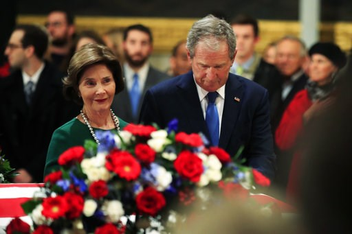 (AP Photo/Manuel Balce Ceneta). Former President George W. Bush and former first lady Laura Bush pay their respect to his father former President George H.W. Bush as he lie in state at the U.S. Capitol in Washington, Tuesday, Dec. 4, 2018.