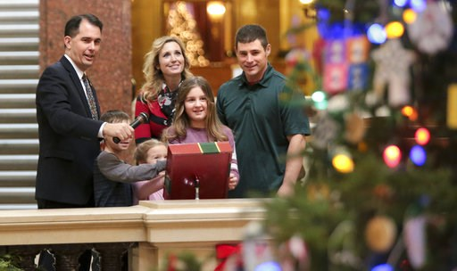 (Steve Apps/Wisconsin State Journal via AP). Wisconsin Gov. Scott Walker, left, with the help of the Mary and Don Miller family from Plainfield, Wis., flipped the switch to light the state Christmas Tree in the Capitol Rotunda, Tuesday, Dec. 4, 2018 at...
