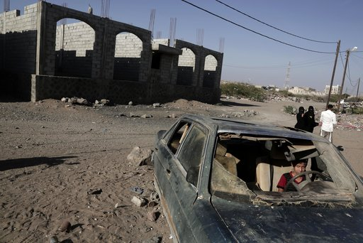 (AP Photo/Nariman El-Mofty, File). FILE - In this Feb. 10, 2018 file photo, a boy sits in a damaged car in Mocha, Yemen. Envoys from Yemen's warring parties are headed to Sweden for another round of peace talks to stop the three-year-old war, but with ...