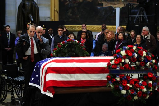 (AP Photo/Manuel Balce Ceneta). Former Sen. Bob Dole salutes the flag-draped casket containing the remains of former President George H.W. Bush as he lies in state at the U.S. Capitol in Washington, Tuesday, Dec. 4, 2018.