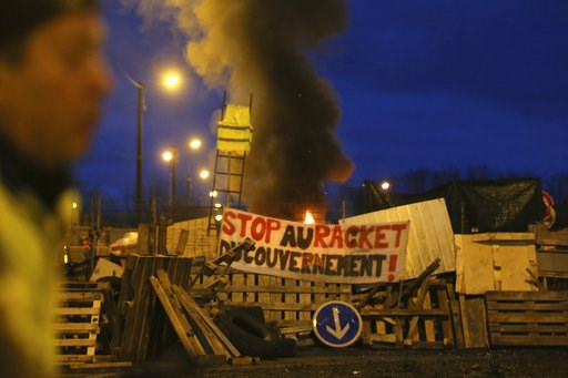 "(AP Photo/David Vincent). A demonstrator stands in front of a makeshift barricade set up by the so-called yellow jackets to block the entrance of a fuel depot in Le Mans, western France, Tuesday, Dec. 5, 2018, with banner reading ""Stop the Government r..."