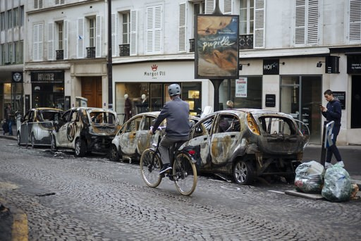 (AP Foto/Kamil Zihnioglu). Un individuo coonduce su bicicleta frente a automóviles incendiados cerca del Arco del Triunfo en París, Francia, el domingo 2 de diciembre de 2018. La zona fue sitio de protestas contra la subida de impuestos y el alto costo...