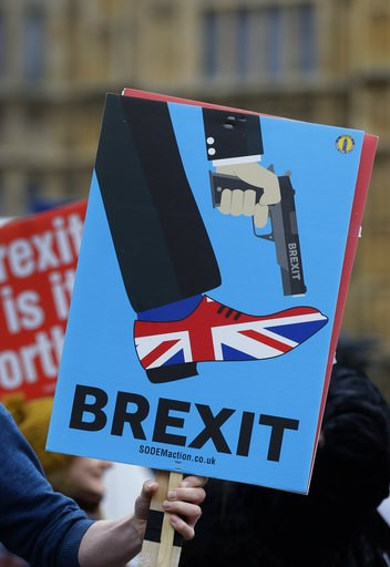 (AP Photo/Kirsty Wigglesworth). An anti-Brexit campaigner holds a banner in front of parliament in London, Wednesday, Dec. 5, 2018. Britain's Brexit debate has become a bruising battle between lawmakers and Prime Minister Theresa May's government. May ...