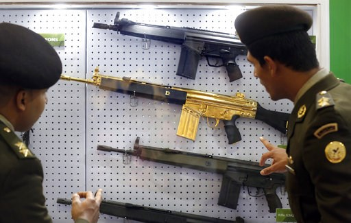 (AP Photo/Amr Nabil). Egyptian army officers look at a gold-plated weapon at the Pakistani booth during the first arms fair organized in Cairo, Egypt, Tuesday, Dec. 4, 2018. The three-day Egypt Defence Expo features the world's top arms companies and h...