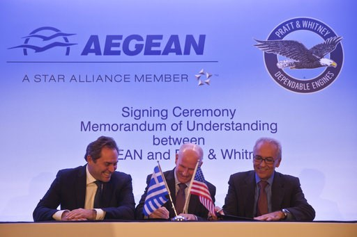 (AP Photo/Petros Giannakouris). Chairman of Aegean Airlines Eftychios Vassilakis, left, Rick Deurloo Senior Vice President - Sales, Marketing and Customer Support at Pratt & Whitney and Aegean Airlines CEO Dimitrios Gerogiannis, right, sign a memor...