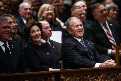 (AP Photo/Evan Vucci). Jeb Bush, Laura Bush, and former President George W. Bush share a laugh as a story is told about former President George H.W. Bush during a State Funeral at the National Cathedral, Wednesday, Dec. 5, 2018, in Washington.