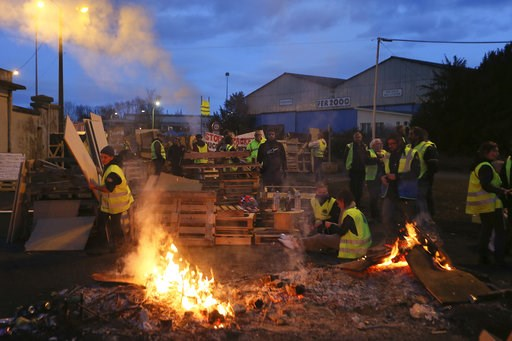 (AP Photo/David Vincent). Demonstrators stand in front of a makeshift barricade set up by the so-called yellow jackets to block the entrance of a fuel depot in Le Mans, western France, Tuesday, Dec. 5, 2018. French government's decision to suspend fuel...