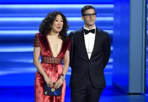 (Photo by Chris Pizzello/Invision/AP, File). FILE - In this Sept. 17, 2018 file photo, Sandra Oh, left, and Andy Samberg present an award at the 70th Primetime Emmy Awards in Los Angeles. Oh and Samberg will share host duties at next month's Golden Glo...